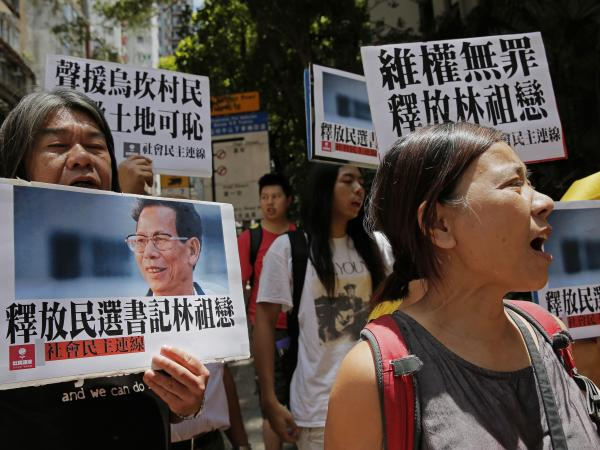 "Protesters in Hong Kong hold signs saying ""Release democratically elected secretary Lin Zulian,"" during a demonstration on Tuesday."