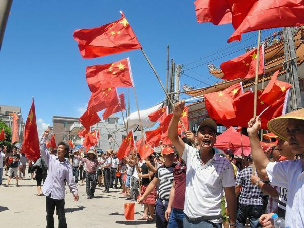 Villagers wave Chinese flags and chant slogans demanding the return of their leader Lin Zulian, the Communist Party secretary of the village, during a protest on June 19 in Wukan. The protests come nearly five years after an uprising there made the village an internationally known symbol of grass-roots defiance.