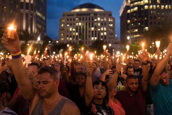 People hold candles during an evening memorial service for the victims of the Pulse Nightclub shootings, at the Dr. Phillips Center for the Performing Arts, June 13, 2016 in Orlando, Florida. The shooting at Pulse Nightclub, which killed 49 people and injured 53, is the worst mass-shooting event in American history. (Drew Angerer/Getty Images)