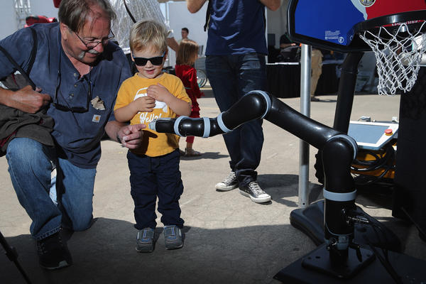 Two-year-old Hunter Kleimo and his grandfather Mike Kleimo interact with a Clearpath Robotics robot at the Defense Advanced Research Projects Agency Robotics Challenge Expo at the Fairplex June 5, 2015 in Pomona, California. (Chip Somodevilla/Getty Images)