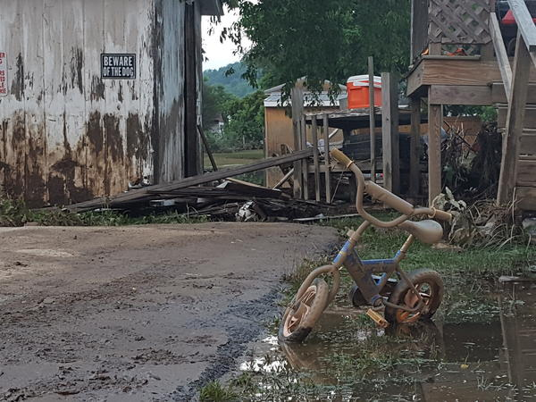 Days after deadly floods swept through West Virginia, everything in the front yard of a home in Rainelle is still caked in mud.