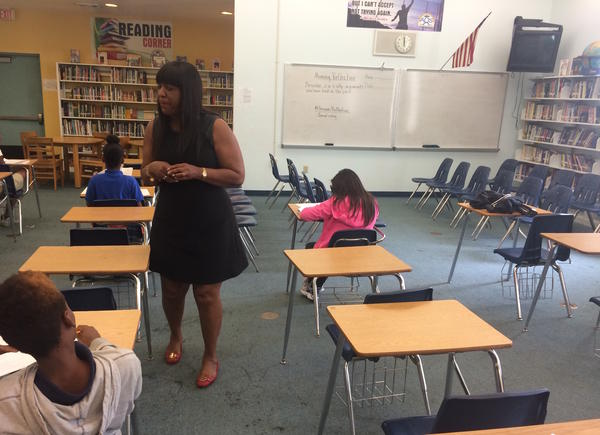 """Students complete self-reflection surveys at the success center at 500 Rolemodels academy. A prompt on the whiteboard says: """"Describe 2 or 3 silly arguments you have had in the past"""""""