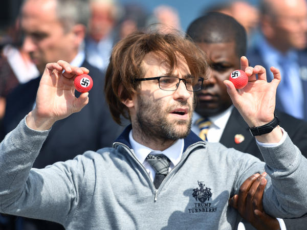 Comedian Lee Nelson is taken away by security Friday while holding golf balls stamped with swastikas, as he protests Donald Trump, at the opening of Trump's resort in Scotland.