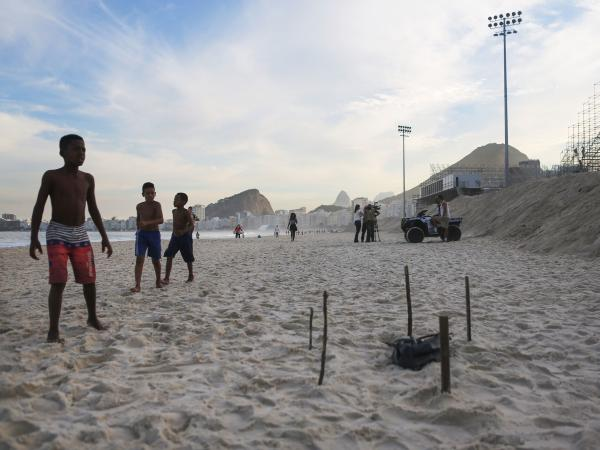 Young beachgoers walk near a body part covered in a plastic bag, which was discovered on Rio's Copacabana Beach near the Olympic beach volleyball venue on Wednesday. The Rio 2016 Olympic Games begin August 5.