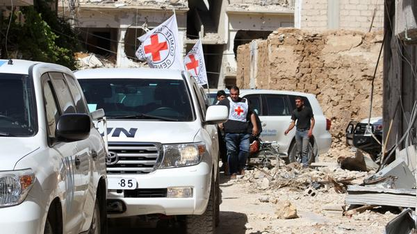 Vehicles of the International Committee of the Red Cross and the United Nations wait after an aid convoy entered the rebel-held town of Daraya, near Damascus, on June 1. It was the first such delivery since a government siege began in 2012, the Red Cross said. But the opposition said only medical supplies were in the delivery, not desperately needed food.