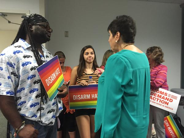 """Members from the activist group """"Moms Dedicated To Action"""" held signs that read """"Disarm Hate"""" at the news conference at the Ft. Lauderdale airport Tuesday morning."""
