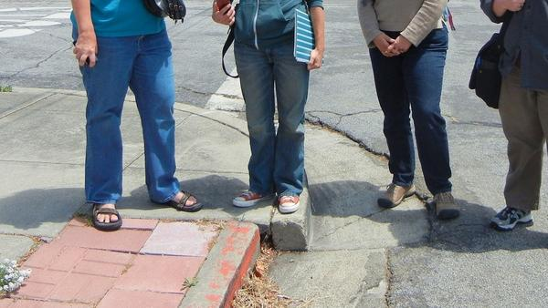 Geology enthusiasts gather at a (formerly) noteworthy curb in Hayward, Calif., in May 2012. The curb was once straight; the shifting Hayward fault pulled it apart.