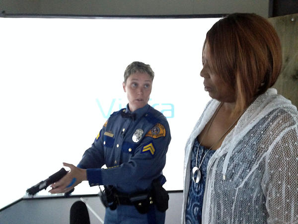 Washington State Patrol Corporal Lori Hinds shows Karen Johnson of the Black Alliance of Thurston County how to fire a pistol. Johnson was about to experience a high-tech deadly force simulator at the State Patrol academy in Shelton.