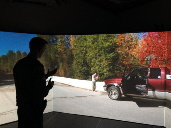 Washington State Patrol Corporal Brandon Dumont, an instructor at the Patrol's academy in Shelton, demonstrates de-escalation tactics while using a video simulator.