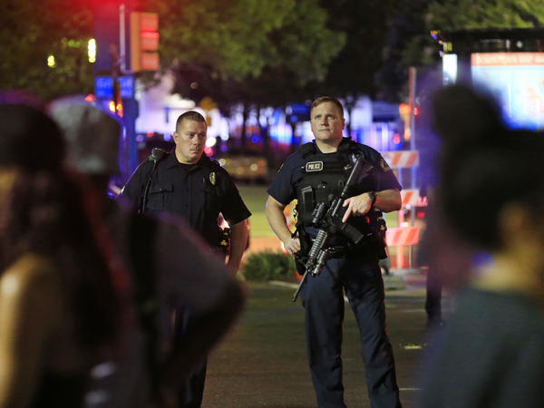 Dallas police and residents stand near the scene where officers were shot and killed on Thursday in Dallas.