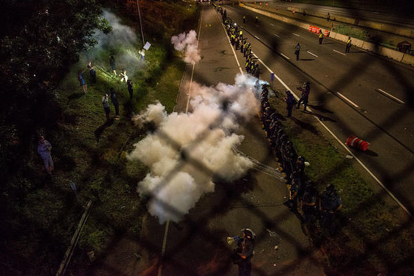 Police officers launch smoke bombs and tear gas to clear out protesters who shut down highway I-94 on Saturday in St. Paul, Minnesota.