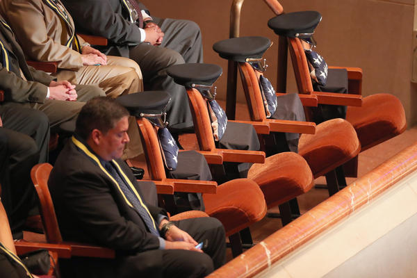 Reserved seats at the memorial service contain American flags and police hats to honor the five slain officers.