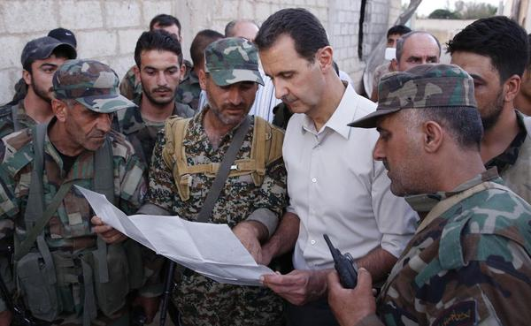 Syrian President Bashar Assad (white shirt) speaks with Syrian troops in the suburbs of Damascus on June 26, in a photo released by the official SANA news agency. The U.S. and Russia are working on a proposal to coordinate their bombing campaigns in Syria, where the two powers are fighting the Islamic State and other Islamist extremists.