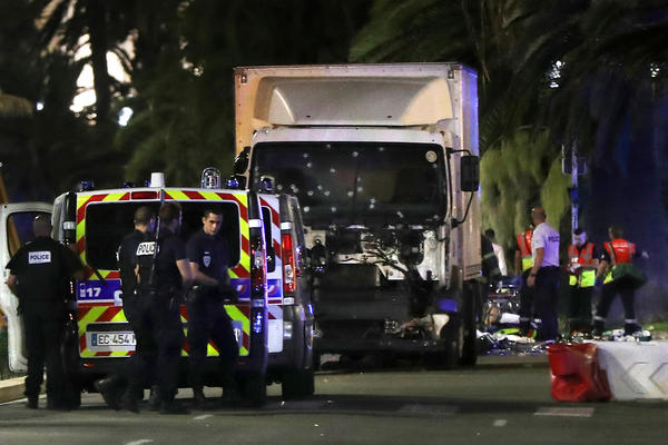 Police officers and rescue workers stand near the truck used in the attack in Nice on Thursday evening. The former mayor of Nice said dozens of people were killed in the attack. He urged residents to stay indoors.