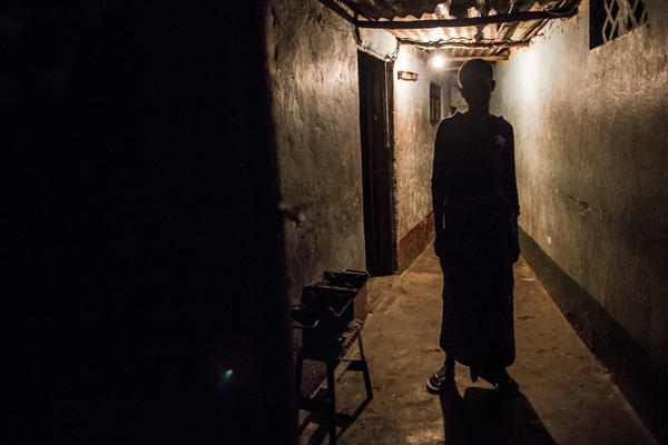 A sex worker waits outside a room she rents in Beira, Mozambique. Her client, inside, will pay 50 meticais for 5 minutes with her — that's about 75 cents.