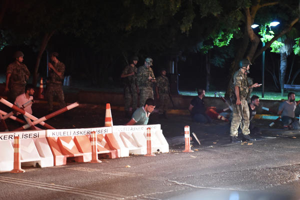Turkish security officers detain unidentified individuals on the side of the road on Friday in Istanbul, during a shutdown of the Bosporus bridge.
