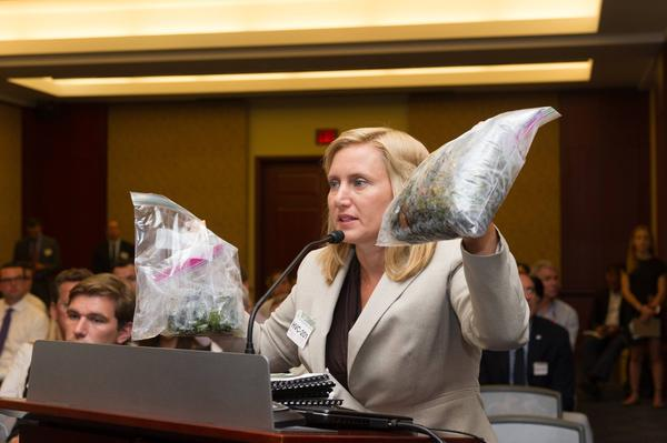 The Conservancy of Southwest Florida's Jennifer Hecker holding up toxic algae samples from Florida at a meeting with federal lawmakers in Washington DC this week.