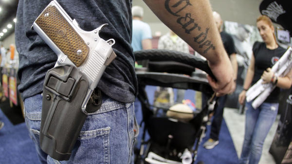 Donald Carder wears his handgun in a holster as he pushes his son, Waylon, in a stroller at the National Rifle Association convention in Louisville, Ky., in May. Attendees at the convention are permitted to carry firearms under Kentucky's open-carry law.