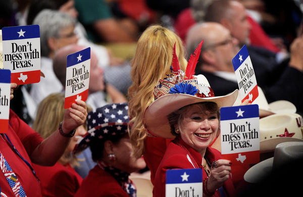 "Delegates from Texas hold ""Don't mess with Texas"" signs on Tuesday at the Republican National Convention."