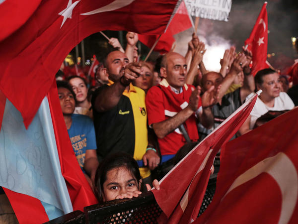 People wave Turkish flags as they gather in Taksim Square in Istanbul, protesting against the attempted coup on Wednesday. Turkish President Recep Tayyip Erdogan declared a 3-month state of emergency.