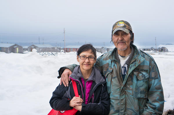 Sandra Gologergen and Wilfred Miklahook stand with the community of Savoonga, Alaska, in the background. Despite what appears to be lots of snow, Savoonga residents have been struggling with warmer-than-usual temperatures, which has led to challenging conditions for subsistence hunting.
