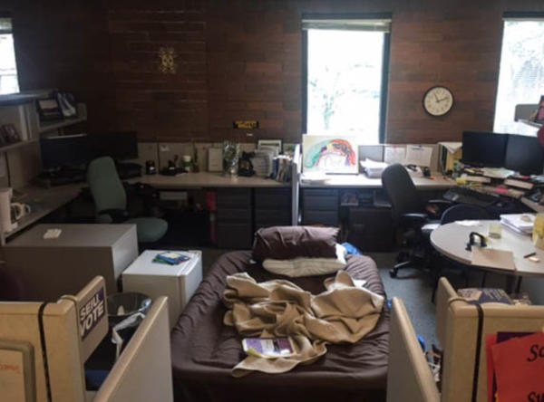 <p>A cot, squeezed in among office cubicles at a child abuse hotline office, where a teen slept back in June.</p>