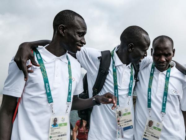 South Sudan's James Nyang Chiengjiek (left) and Yiech Pur Biel speak with Kenyan coach Joseph Domongole at the iconic statue of Christ the Redeemer in Rio de Janeiro on July 30. South Sudan, which became independent in 2011, will have three runners competing in the country's first Olympic Games.