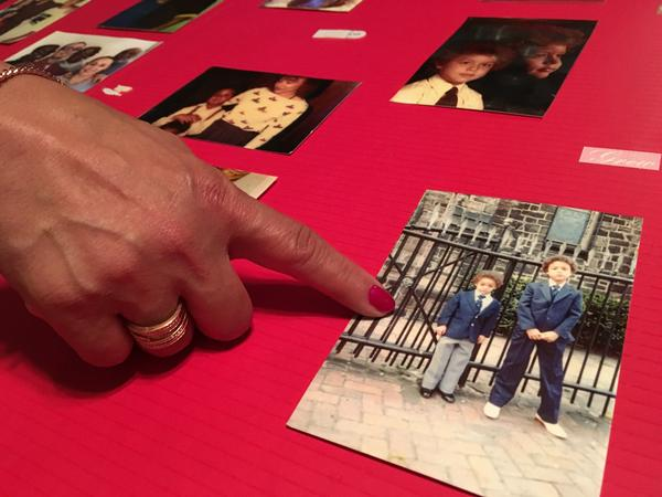Anita Colon looks at photos of her brother Robert and other family members when he was younger. (Sam Fields/Here & Now)