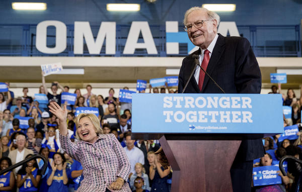 Berkshire Hathaway Chairman and CEO Warren Buffett stands at the lectern during a Hillary Clinton campaign event in Omaha, Neb. Clinton waves in the background.