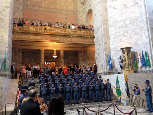 Families, friends and state officials applaud the 106th graduating class of Washington State Patrol troopers at a graduation ceremony at the state Capitol. These new troopers will help make a small dent in a large trooper shortage.