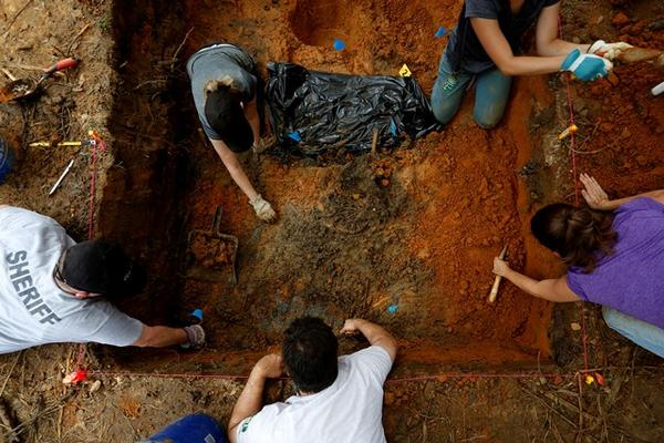 In this file photo from August 2013, USF investigators conduct exhumation work in a cemetery on the Marianna, FL, campus of the Dozier School for Boys.