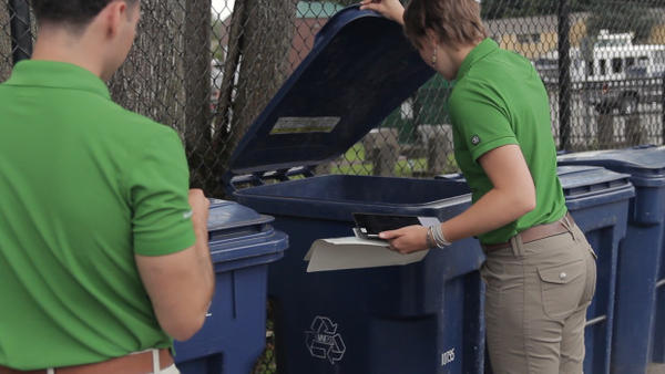 <p>Interns Audrey Taber and Crhistian Cuellar examine the contents of the recycling bins at Parkview Apartments in Auburn, Washington to find potential topics for conversation with residents.</p>