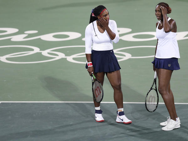 Venus Williams (right), of the United States, talks with her sister Serena after losing a point in a doubles match against Lucie Safarova and Barbora Strycova, of the Czech Republic.