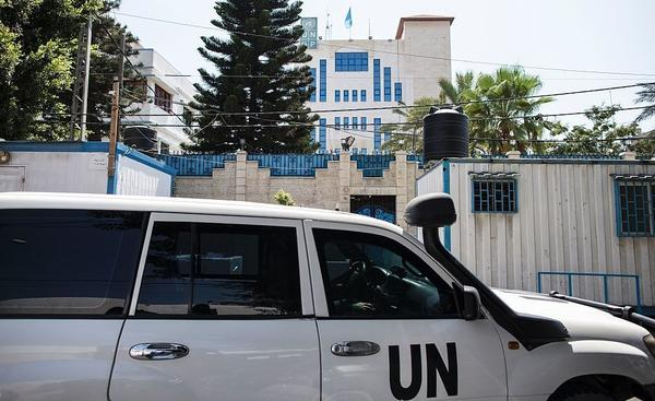 Palestinian staff of the United Nations Development Programme drive an official car in front of its headquarters in Gaza City on Tuesday.