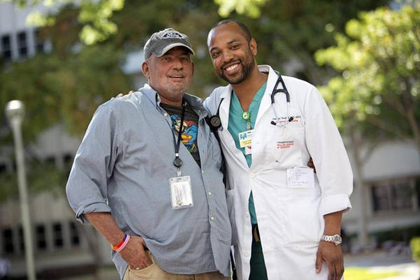 Jose De Lemos, 53, and Dr. Hansel Tookes, a University of Miami medical resident, outside of Jackson Memorial Hospital after a recent visit. De Lemos, who has HIV, is being treated by Tookes.