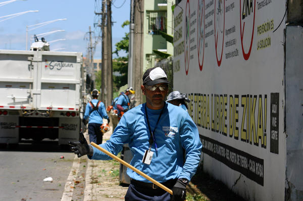 A city worker in San Juan, Puerto Rico cleans up a vacant lot where mosquitoes could be breeding.