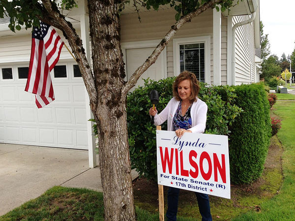 Republican Lynda Wilson of Vancouver pounds a campaign sign into the yard of a supporter. She's a current state representative running for the state Senate against Democrat Tim Probst in one of the most competitive legislative races this year.