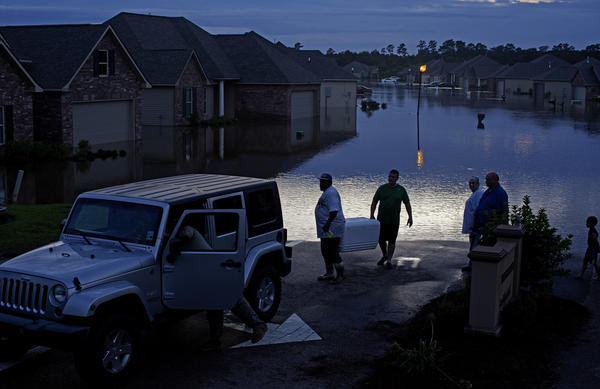 Residents evacuate with food in ice chests in Hammond, La., on Saturday.