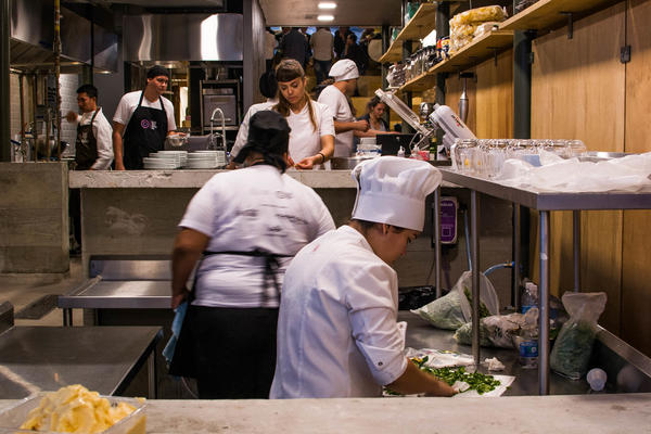Cooks prepare a dinner for gourmet soup kitchen that feeds people with what society has thrown away as leftovers. This concept was created by chef Massimo Bottura at his restaurant RefettoRio Gastromotiva in Rio de Janeiro.