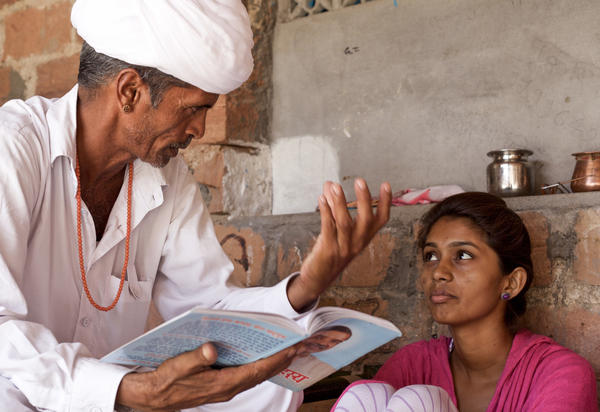 Lumbaram reads aloud to Durga from a philosophy book. Since he started his effort to rescue her from her marriage, the two have grown close.