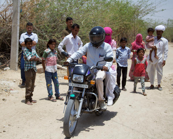 Lumbaram, in white turban holding a child, watches as his brother drives Durga to Jodhpur for her exams.