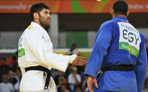 Israel's Or Sasson (left) ties to shake hands with Egypt's Islam Elshehaby during their men's 100kg judo contest match on Aug. 12.