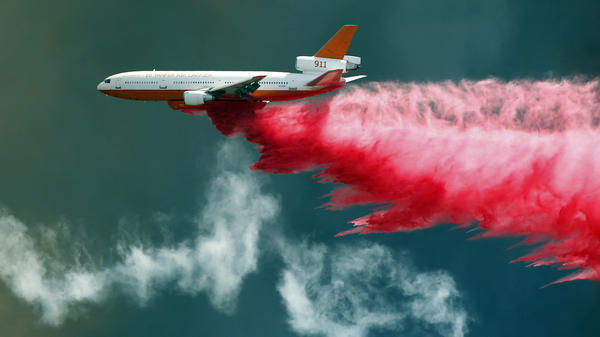 An air tanker fights California's Bluecut wildfire with flame retardant. Fire experts say Bluecut has burned and spread with a ferocity they've never seen before.