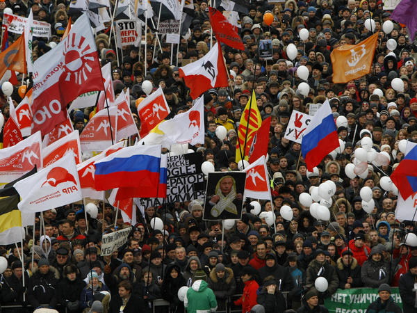 Demonstrators hold Russian opposition flags during a rally protesting against election fraud in Moscow, Saturday, Dec. 24, 2011. Russian President Vladimir Putin blames Hillary Clinton for protests like this, which took place in 2011 and 2012.