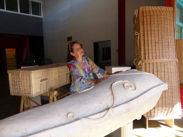 <p>Cynthia Beal stands beside her own casket, an eco-pod made of recycled newspapers. She decorated it herself. The coffins behind Beal are made of bamboo and woven willow. All completely bio-degradable.</p>