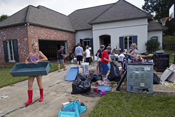 Raven Harelson, 59, (left) carries a drawer to the trash heap in front the home of Sheila Siener, 58, as friends and family help to clean out the flood damaged home in St. Amant, La., on Saturday.
