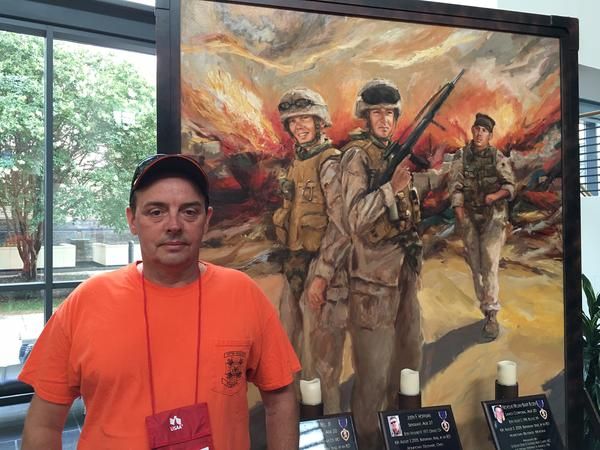 At the VFW convention, Ed Hendrickson of Norfolk, Va. stands beside a painting of troops killed in action.