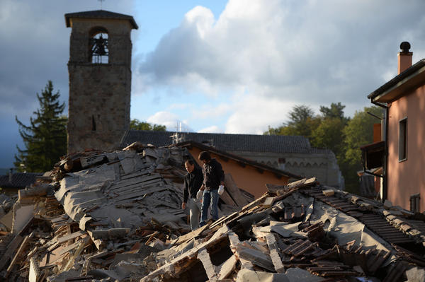 Two men walk on a damaged home after a strong earthquake hit Amatrice, Italy, on Wednesday.