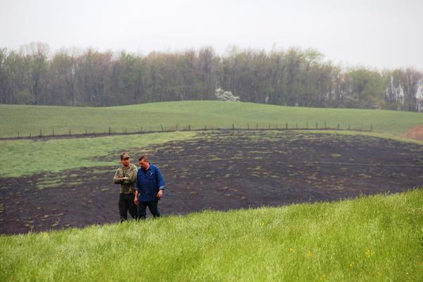 Two men walk the scene of a natural gas transmission line explosion in western Pennsylvania, April 29, 2016. The blast was so powerful it ripped a 12-foot crater into the landscape and burned a section of the field with a quarter-mile radius.