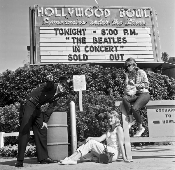 Officer Robert Yocum informs Beatle fans Chelie Mylott and Melody Yapscott, right, that they'll have to move from their spot in front of the Hollywood Bowl. The women had no tickets but hoped to get them from scalpers or sneak in. This photo was published in the Aug. 24, 1964 <em>Los Angeles Times</em>.